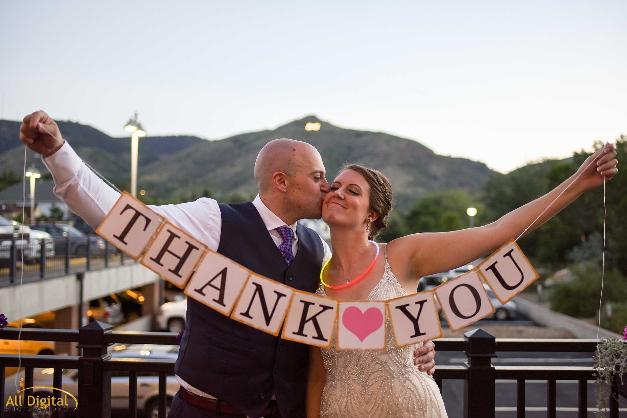 Mary & Jeremy holding up a Thank You sign during their wedding at the Golden Hotel. Photographed by All Digital Studios